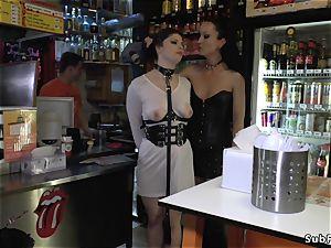domme in leather predominates gimp in public