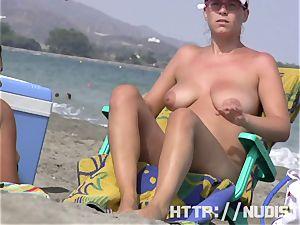 Having joy posing on public nudist beach